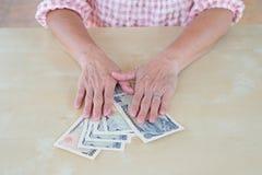 Remettez la femme avec les billets de banque et la pièce de monnaie japonais de Yens de devise Photos stock
