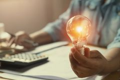 remettez la femme comptable tenant l'ampoule, nouvelle idée avec l'innovati photo libre de droits