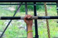 Remettez la fille avec une manucure sur une barre de fer avec les veines et la MU tendues photo libre de droits