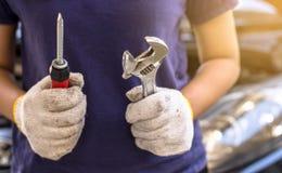 Remettez la fixation d'ingénieur de mécanicien, technicien de voiture tenant le tournevis et la clé, entretien de voiture de conc Photographie stock