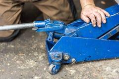 Remettez la grue de voiture et le mécanicien de voiture dans le garage Image stock
