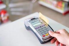 Remettez la presse avec frapper à toute volée la carte de crédit sur le terminal de paiement dans le magasin image libre de droits