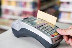 Remettez la presse avec frapper à toute volée la carte de crédit sur le terminal de paiement dans le magasin photo libre de droits