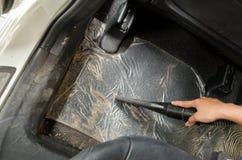 Remettez la saleté de nettoyage de vide sur un tapis de voiture Images libres de droits