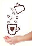 Remettez la tasse de café de prise complètement de grains de café avec des formes de coeur Photos stock