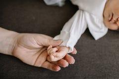 Remettez le bébé dans la main du plan rapproché de mère amour de concept de famille Photo stock