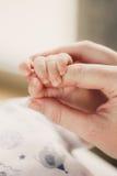 Remettez le bébé de sommeil dans la main de la fin de mère Photographie stock