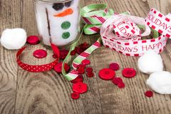 Remettez le bonhomme de neige, le ruban de métier de Noël, et les boutons ouvrés, s'étendant sur un fond en bois de grain Image libre de droits