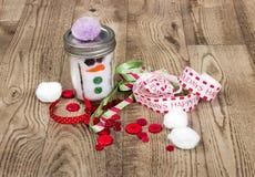 Remettez le bonhomme de neige, le ruban de métier de Noël, et les boutons ouvrés, s'étendant sur un fond en bois de grain Images libres de droits
