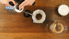 Remettez le café d'égouttement, l'eau de versement de barman sur le marc de café avec le filtre Photographie stock libre de droits