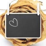 Remettez le coeur de dessin sur le tableau noir avec le fond sec de rose de blanc, Images libres de droits