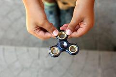 Remettez le fileur ou le fileur remuant tournant sur la main du ` s d'enfant Photographie stock