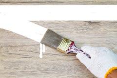 Remettez le gant blanc de port tenant le vieux pinceau grunge et Image stock
