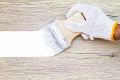 Remettez le gant blanc de port tenant le vieux pinceau grunge et le peignant sur le mur en bois Photos libres de droits