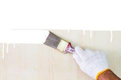 Remettez le gant blanc de port tenant le vieux pinceau grunge et le peignant sur le mur en bois Image stock