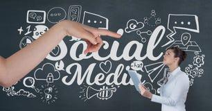 Remettez le pointage à la femme d'affaires tenant un comprimé sur le fond bleu avec les icônes sociales de media Photographie stock libre de droits