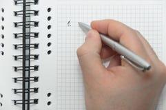 Remettez le premier élément d'écriture dans la liste sur le cahier Image stock