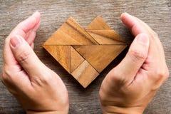 Remettez le puzzle de tangram de couverture dans la forme de coeur sur le fond en bois Photo stock