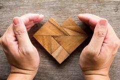 Remettez le puzzle de tangram de couverture dans la forme de coeur sur le fond en bois Image stock