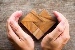 Remettez le puzzle de tangram de couverture dans la forme de coeur sur le fond en bois Photo libre de droits