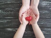 Remettez le rouge de coeur de papa et d'enfant sur en bois noir photos stock