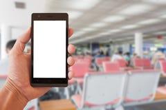 Remettez le smartphone de prise avec les personnes troubles attendant le vol dans l'aéroport local Images stock