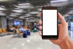 Remettez le smartphone de prise avec les personnes troubles attendant le vol dans l'aéroport local Images libres de droits
