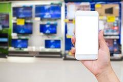 Remettez le smartphone de prise avec le magasin eletronic de tache floue Photos stock