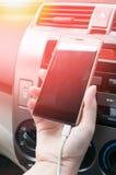 Remettez le smartphone de prise dans la voiture, téléphone de prise de chargeur sur la voiture Photo libre de droits