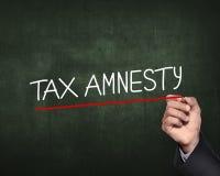 Remettez le stylo de participation et écrivez les mots d'amnistie d'impôt Photographie stock libre de droits