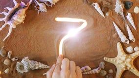 Remettez le symbole 7 du numéro de dessin sept dans le sable Seashell de feston sur le rose Vue supérieure banque de vidéos