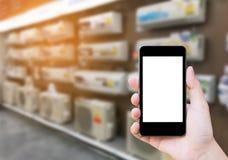 Remettez le téléphone portable de prise avec le climatiseur dans le magasin électronique Images stock