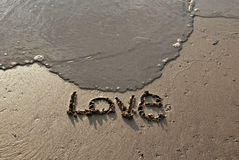 Remettez le texte de 'amour' de writte sur la plage Photo stock