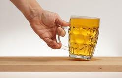Remettez le verre de prise de bière blonde de conseil en bois image libre de droits
