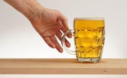 Remettez le verre de prise de bière blonde de conseil en bois photo libre de droits