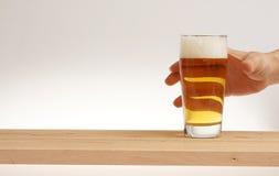 Remettez le verre de prise de bière blonde de conseil en bois photos stock