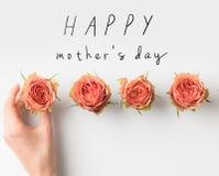 remettez les bourgeons émouvants de rose de rose placés dans la rangée avec l'inscription HEUREUSE de JOUR de MÈRES image libre de droits