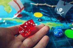 Remettez les matrices rouges de lancement sur la carte du monde des jeux de société faits main de terrain de jeu avec un bateau d Photo stock