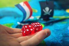 Remettez les matrices rouges de lancement sur la carte du monde des jeux de société faits main de terrain de jeu avec un bateau d Image stock