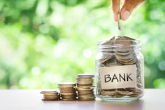 Remettez mettre des pièces de monnaie dans le pot en verre avec le mot de banque Photos stock