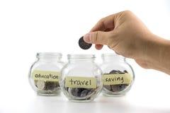 Remettez mettre la pièce de monnaie dans le récipient en verre avec des labels de voyage, d'économie et d'éducation Images libres de droits