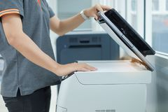 Remettez mettre un papier de document dans la machine de copie de scanner ou de laser d'imprimante dans le bureau images libres de droits