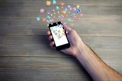 remettez montrer des hologrammes d'icônes sur l'écran d'un smartphone sur le fond en bois Photographie stock libre de droits