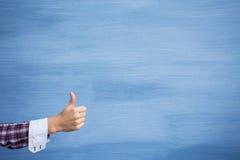 Remettez montrer des pouces vers le haut de geste sur le fond bleu Images libres de droits