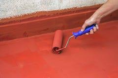 Remettez peindre un plancher rouge avec un rouleau de peinture Photo stock