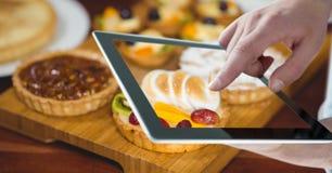 Remettez photographier des tartes par le comprimé numérique à la boulangerie photo libre de droits