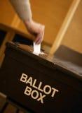 Remettez placer le vote dans l'urne dans le bureau de vote Photographie stock