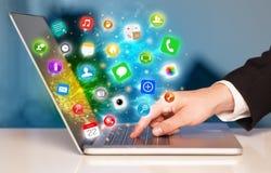 Remettez presser l'ordinateur portable moderne avec les icônes mobiles et les symboles d'APP Photographie stock libre de droits