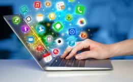 Remettez presser l'ordinateur portable moderne avec les icônes mobiles et les symboles d'APP Photographie stock