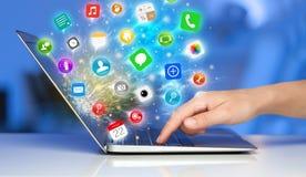Remettez presser l'ordinateur portable moderne avec les icônes mobiles et les symboles d'APP Photo libre de droits